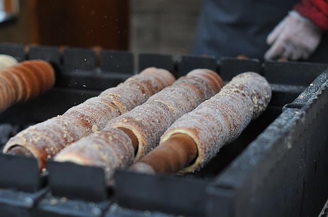 Trdelníky werden traditionell auf Buchenholz (trdlo) - neuerdings auch auf Metallzylindern - über offenem Feuer gedreht und gebacken.