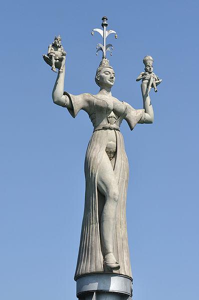 """Imperia-Statue im Hafen von Konstanz am Bodensee (aufgestellt 1993). In ihren Händen hält sie laut ausführendem Bildhauer """"nackte Gaukler"""", die sich die Insignien der weltlichen und geistlichen Macht widerrechtlich aufgesetzt haben. © Dietrich Krieger, CC BY-SA 3.0"""